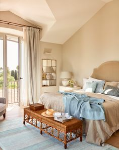 00428898. Dormitorio clásico con gran cabecero tapizado, espejo y banco de mimbre 00428898