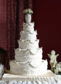 White Victorian style five tier white wedding cake decorted with classic scrolls