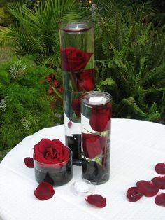 wedding centerpieces DIY different size tornado vases Red flowers ( for this the HAVE to be REAL) black stone/marbles floating candles. small gears extra petals (put marbles in first Use a chopstick to gently press flowers to bottom while you fill with water and you have to have a floating candle for top to help hold the flowers down, sprinkle petals and gears around base)