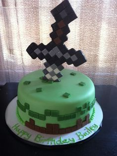 Minecraft cake. This should be square like everything else in minecraft...and solid green cake piped with brown icing at the base would be sufficient...I'd just cut down one of the foam swords and set it so it appears to be plunging into the top....