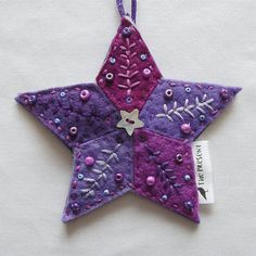 Felt Star Decoration, entirely hand cut and stitched. 5 diamond shapes in 5 shades of purple felt, stitched onto a purple felt backing, with an additional layer of thick felt inside to give it body. Embroidered in 5 different complementary shades of purple thread, embellished with a