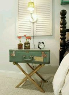 I love the shutters. A blue suitcase on top of a suitcase holder for a night table