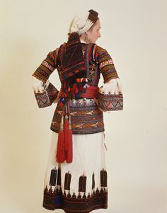 The costume of Perachora, Corinthia, Peloponnese is probably typical for the whole of Peloponnese (in variations) and central Greece. It consists of a chemise, a short-sleeved bodice, a girdle and a white sleeveless short coat. The headdress has a long embroidered scarf worn loosely round the head like a turban.