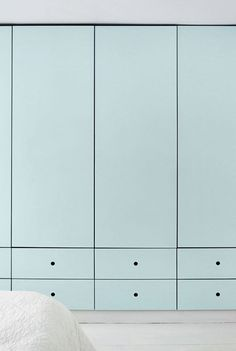 Den minimalistiske skabsvæg har låger med mintgrøn linoleum. Her er der god plads til familiens tøj.  Skabe fra Københavns Møbelsnedkeri