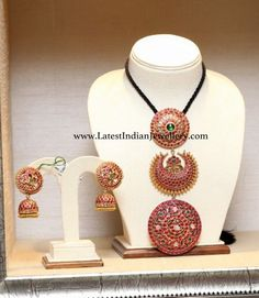Traditional yet unique 3 step ruby pendant with surya chandra and rakodi motifs which are typically used as hair accessories. Paired with ruby jhumkas with round large ear tops. Antic Jewellery, Gold Temple Jewellery, Gold Jewellery Design, Jewellery Earrings, Ruby Pendant, Emerald Jewelry, Jewelry Patterns, Indian Jewelry, Bridal Jewelry