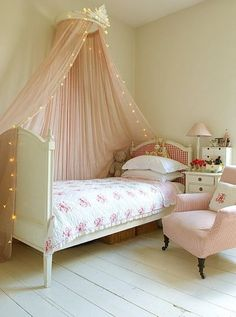 Girl bedroom decor with a soft tulle canopy and twinkle lights