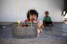 A Syrian refugee child reacts while sitting in a swing in Al Zaatari refugee camp, in the Jordanian city of Mafraq, near the border with Syria, September 19, 2015. REUTERS/Muhammad Hamed