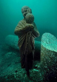 The statue of an Isis priest holding an Osiris jar. It was found on the sunken island of Antirhodos in the ancient harbor of Alexandria. The statue is made from black granite. 4th C. BCE - 4th C. A.D.