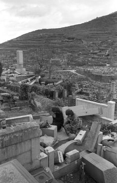 Two women pay respects at a ruined cemetery, Nagasaki, 1945.