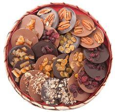 Caja con mendiants o discos de chocolate cubiertos de frutos secos.