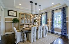 These gorgeous, hanging light fixtures create a beautiful focal point in this rustic chic dining room. | Pulte Homes