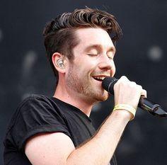 Dan Smith of Bastille smiling happy singing