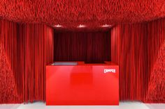 Brazilian architect Marko Brajovic has filled the new Camper store in Milan with thousands of red shoelaces attached on the undulating ceiling.