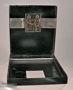 Metal cigarette case with a relief portrait of a German and an Austrian soldier shaking hands. Trench Art