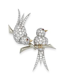 A diamond bird brooch, by Van Cleef & Arpels, circa 1965 The brilliant-cut diamond birds, with ruby eyes, balanced on a perch, diamonds approximately 2.80 carats total, signed Van Cleef & Arpels, numbered, French assay marks, length 5.4cm
