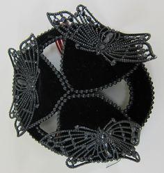 "Hatlet of black velvet with beads and cut-steel butterflies. Black velvet hatlet, the slightly domed openwork crown formed by three ""teardrop"" shapes of black velvet edged with black beads, connected at the points, and connected at bottom edges with short curved black velvet ""bridges"" also edged with black beads. In each of the teardrop sections is set a large black stamped metal ""cut steel"" style butterfly. Evidence of black net veil, now missing. Interior ..."