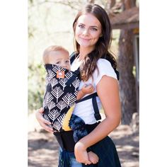 Tula Baby - Ergonomic Carrier - Argol Explore new sights and sounds in 'Arbol'. This simple, modern design stands out with its monochrome scene and bright colored leg padding. 'Arbol' has a pattern of white tree-like outlines on a black background and richly colored yellow leg padding with a plus sign pattern. The neutral, hip design against black canvas can seamlessly work with any style.