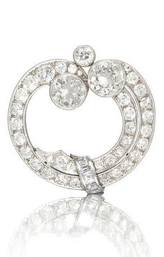 An Art Deco diamond annular brooch, circa 1920. Designed as stylised rolling waves, set with old brilliant and square-cut diamonds, each issuing a larger old brilliant-cut diamond, mounted in platinum and gold, diamonds approximately 7.10 carats total, Dutch assay mark. #ArtDeco #brooch