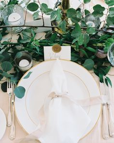 Each place card was calligraphed by Margaret's stepmom and featured the couple's gold wax seal. Gold-rimmed plates held delicately tied napkins.
