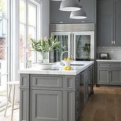 Gray Kitchen Photos Contemporary Minimalist Modern Kitchen: A classic kitchen with French doors, gray cabinetry, Sub-Zero refrigerators, pendant lamps, and a Carrera Oro marble island. The post Gray Kitchen Photos appeared first on Dome Decoration. Farmhouse Kitchen Cabinets, Modern Farmhouse Kitchens, Kitchen Cabinet Design, Island Kitchen, Kitchen Countertops, Kitchen Layout, Colonial Kitchen, Farmhouse Style, Kitchen Flooring