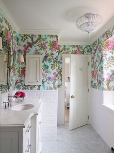 Stunning white bathroom with colorful wallpaper.