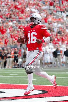 News Photo : J.T. Barrett of the Ohio State Buckeyes scores a...