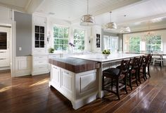 Beautiful kitchen with white cabinets accented with nickel pulls alongside Calacatta marble ...
