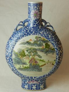 Lot 203: A finely decorated antique Chinese blue & white moon flask vase with a circular Famille Verte panel (est £400 - 700)