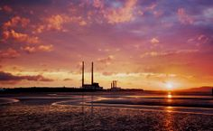 A photograph by photographer Niall O Cleirigh of Sunrise at the strand showing the Red and white chimneys silhouetted by the bright and colou. Red And White, Sunrise, Clouds, Silhouette, Bright, Play, Photography, Outdoor, Outdoors