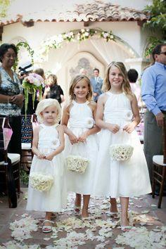 Para una boda al aire libre, frescos vestidos blancos con rosa a un lado, adornado con canastas de flores