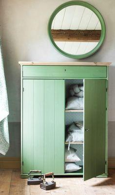 Un armario verde con una puerta abierta mostrando unos artículos textiles en las baldas con un espejo de pared redondo de color verde montado encima.
