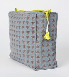 Large enough to fit travel-sized shampoos in addition to makeup brushes and cosmetics, this toiletry bag keeps it all together on the road. A hidden vinyl lining protects the contents of your packed bags from spills and leaks, and the top zip holds everything in neatly. The sturdy dusty blue canvas features a hand-drawn block print in steel grey, the muted triangle pattern a backdrop for the bright yellow green zipper and matching tassel.