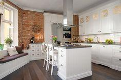 cuisine blanche aménagée avec un îlot central blanc, un plan de travail cuisine en granit gris et décorée de briques de parement