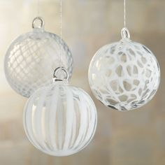This trio of sophisticated art glass ornaments is handcrafted with three complementary designs in white on clear glass: a stylized basketweave, freeform stripes and abstract circles. HandcraftedGlassIntegrated glass hanging loopsMade in China.