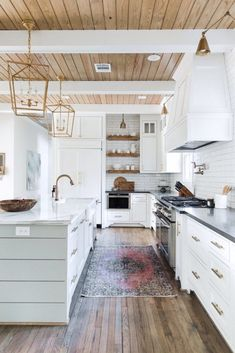 Gorgeous white kitchen with natural wooden ceiling, wooden open shelving, gold accents, and white subway tile. #kitchendesign