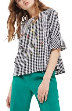 This darling gingham print top with embroidered flowers and flared sleeves is perfect for spring