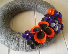 Cute way to welcome the trick-or-treaters!  Wrapped in grey, this wreath has Halloween colored flowers blooming along the side!  Dont like grey? Pick another color!    Perfect on your front door, in your kitchen or on your wall!  Excellent gift for a new home, too!    * This listing is for a 12 wreath as shown    ****This wreath can also be made as a larger wreath!  14 Round $50  16 Round $65    Custom colors can be requested, convo me!    ♥ This and every Itz Fitz! wreath is handmade and…