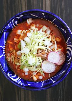 Jalisco-style red pozole made with pork, hominy, guajillo chiles, garlic and more! This soup is garnished with shredded cabbage or iceberg lettuce, radishes, onion and lime juice. Recipe via cocinachronicles.com