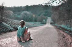 Фото Девушка сидит на дороге и смотрит вдаль