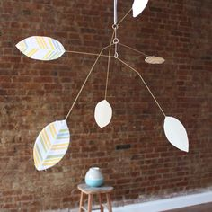 """Super excited about these new brass and paper mobiles. They are so simple and pretty. They swing and sway gently in the breeze.Each leaf if sewn together with a printed side and a solid side - these are the pink pattern with an ivory backing.Overall size is approximately 26"""" x 12"""" deep. Comes in a gift box - ready to hang from 12"""" of ribbon."""