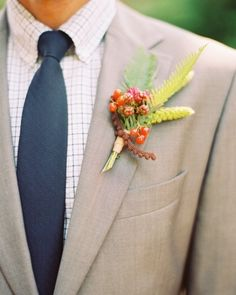A colorful boutonniere of viburnum berries, raspberries, ferns, and millet, tied with ribbon.