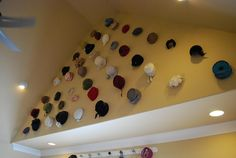 Vintage hat collection display displayed on the vaulted ceiling of a sunroom.