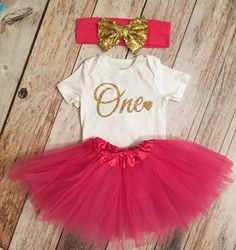 *PLEASE READ SHOP POLICY AND ANNOUNCEMENT FOR CURRENT PRODUCTION AND SHIP TIMES BEFORE PLACING ORDER.*  Let her standout in this beautiful Gold glitter onesie. Made from high quality gold glitter heat transfer vinyl. The hot pink tutu dress is a stretchy to fit newborns and some toddlers. Tulle skirt is about 7.5 long. When relaxed, the waist is about 10 in circumference and will stretch to about 23. Recommended for newborns up to 2 y  Sizes 0-24 months will come as a bodysuit. Sizes 2t and…