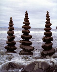 Shiny black rocks for place setting or escort cards. Stacks for each table number with names written on each stone. Andy Goldsworthy.