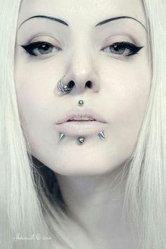 Light, pale makeup. Contrasts. Lip piercings. Alternative goth style.
