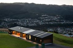 The client called for a house suitable for one person, capable of accommodating guests, an art collection, and entertaining. The brief also called for strategies to enjoy the view out to Porirua Harbour, mitigation of exposure to winds and to develop the landscape of the site. The key concept for the house is that of a wind fence, a long narrow form that is aspected to the north and views, whilst allowing transparency and sunlight to filter inside. This form provides a sheltered outdoor…