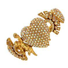 Askew London hinged Clamper Cuff Bracelet; golden winged cherub nymphs holding up sea shells on either side of the center heart, paved in Swarovski Aurora Borealis crystals; inter-spaced with star burst designs, more hearts- all paved with those magical colored faceted crystals, plus a golden flower with a rhinestone center on each end. Marked: Askew London with button logo. Ca. 1980s