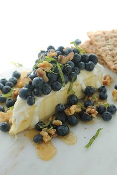 Honey Drizzled Brie with Blueberries, Walnuts and Basil via JennySheaRawn.com. Honey Drizzled Brie with Blueberries, Walnuts and Basil. A gorgeous summer or spring dessert or appetizer that's no-cook and ready in 5 minutes flat. #fruit #spring #easter #mothersdayrecipes #brie #appetizer #blueberrydessert #blueberryrecipe #brierecipe #dessert