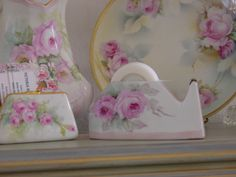 An assortment of surfaces, including a tape dispenser, painted with pink roses by Kathy Carlson.