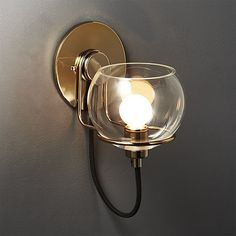 A contemporary take on Italian modern design, glass wall sconce doubles as sculpture and light source. Clear glass globe rests inside minimalist cradle, supported by brass backplate. Glass Wall Sconce, Modern Wall Sconces, Sconce Decor, Candle Holder Wall Sconce, Candle Wall Sconces